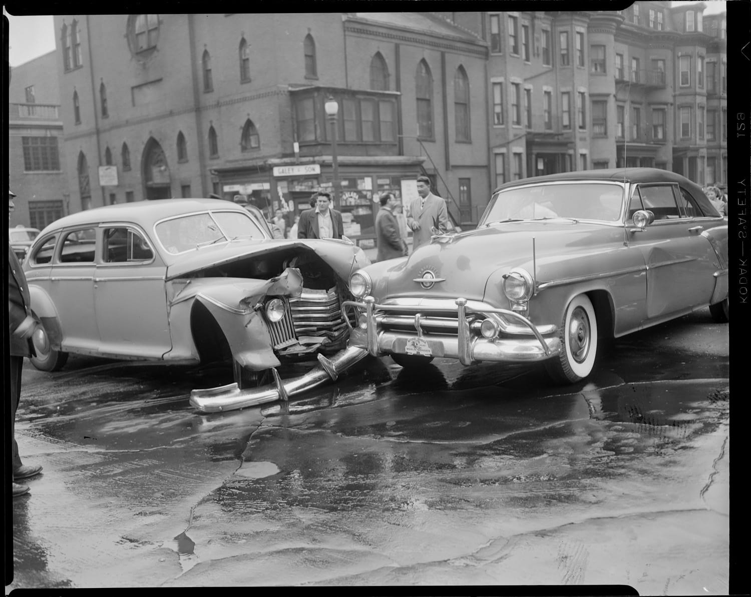 Two old cars collide in a black and white photo