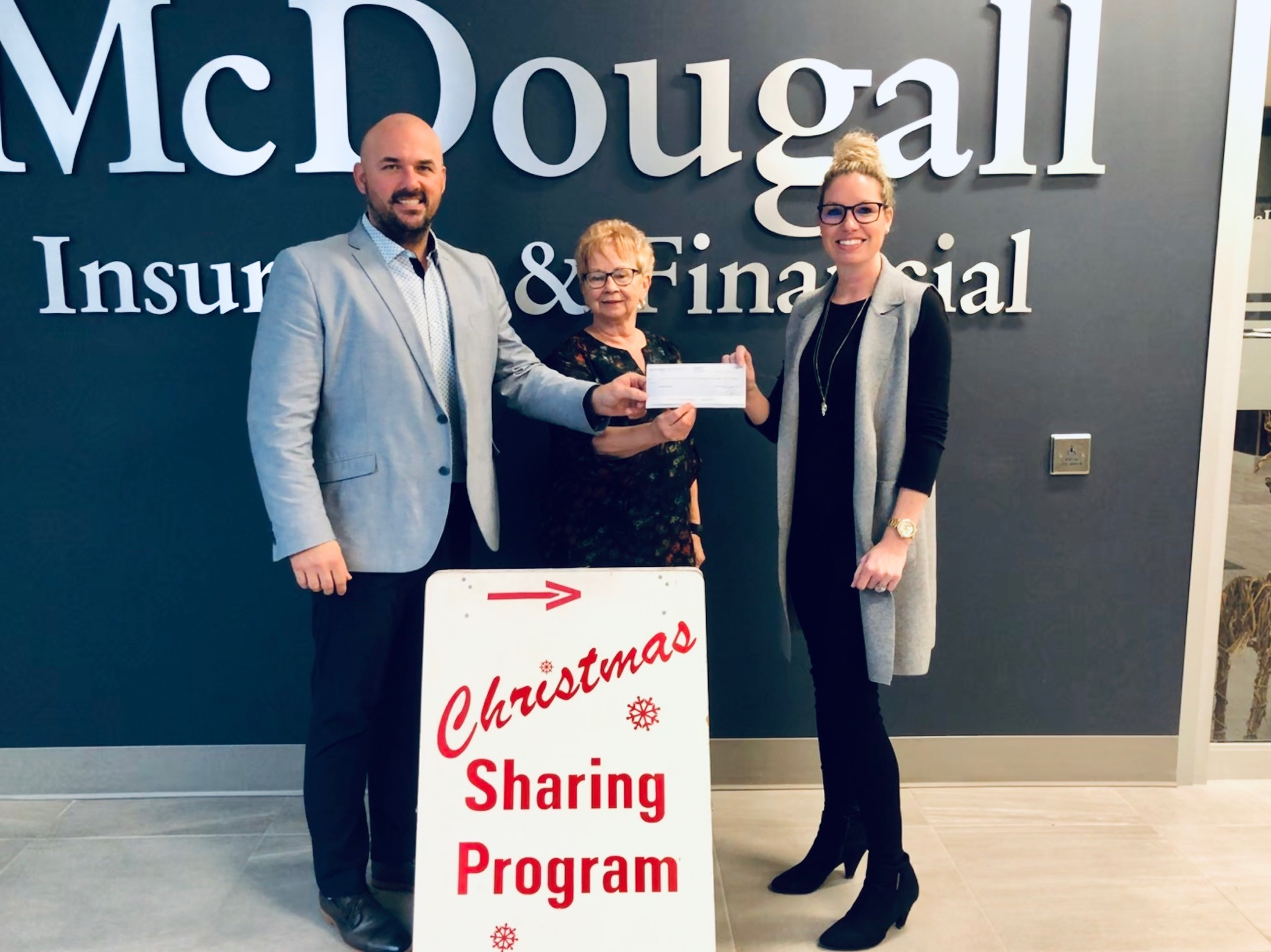 Three people accept cheque from McDougall Belleville to the Christmas Sharing Program