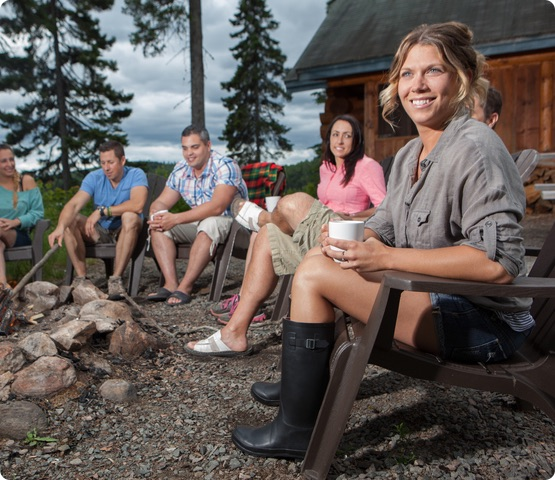 4 people sit outside beside a cottage with trees in the background