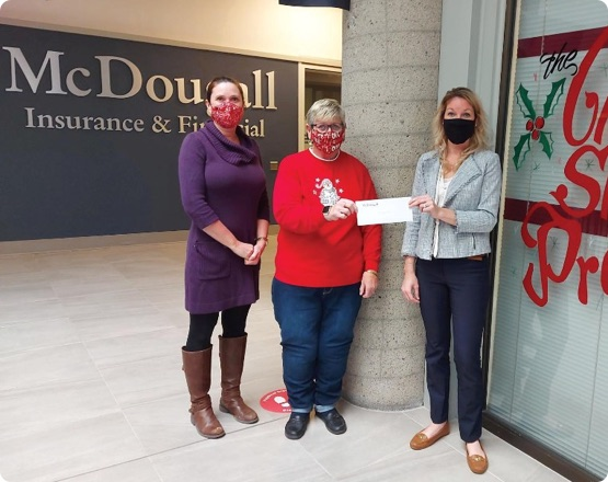 3 people wearing masks holding donation cheque in McDougall office