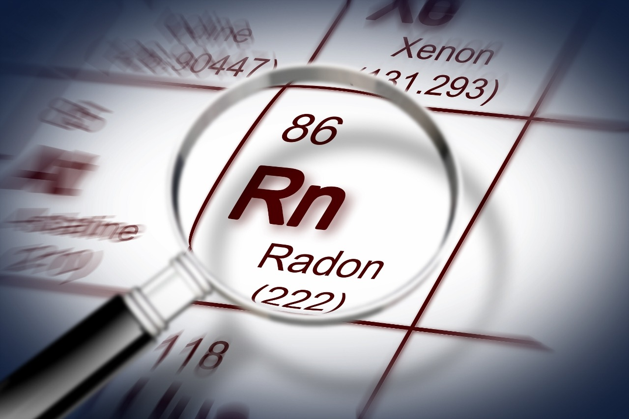Magnifying glass shows close-up of radon as RN (222) on paper