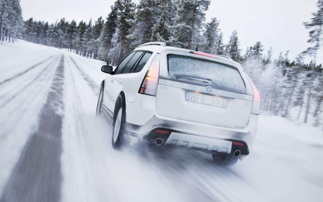 A white SUV drives in winter road conditions